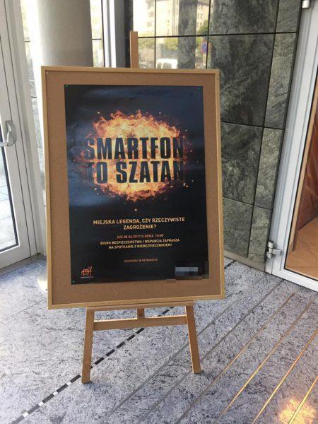 Plakat reklamujący niebezpiecznikowy wykład na korytarzach jednego z klientów.